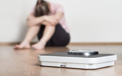 Scale in front of depressed, frustrated, sad woman sitting on floor holding head and arms on knees