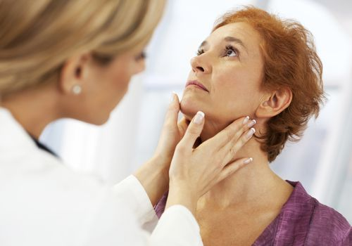 Doctor feeling woman's lymph nodes