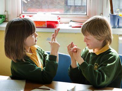 Deaf school children using sign language