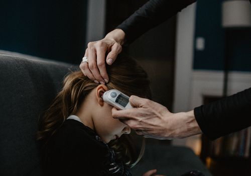 A person taking a child's temperature with an ear thermometer.