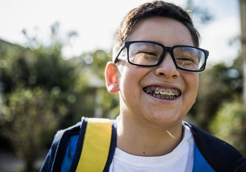 Boy with braces smiling outside