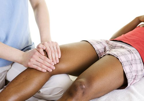 therapist performing physical therapy on client's knee