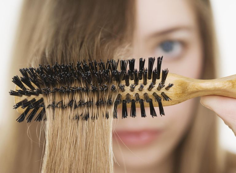 Close up of hairbrush in woman's hair