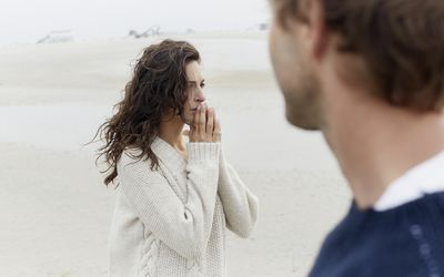 Serious brunette woman and man on the beach
