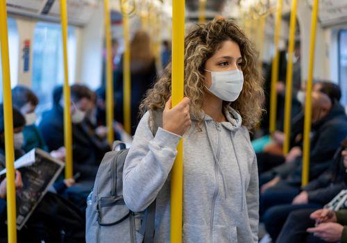 Woman on public transportation wearing a mask.