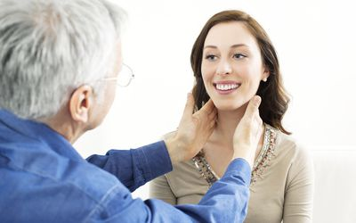 Doctor feeling female patient's thyroid gland