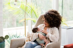 Mom breastfeeds newborn baby