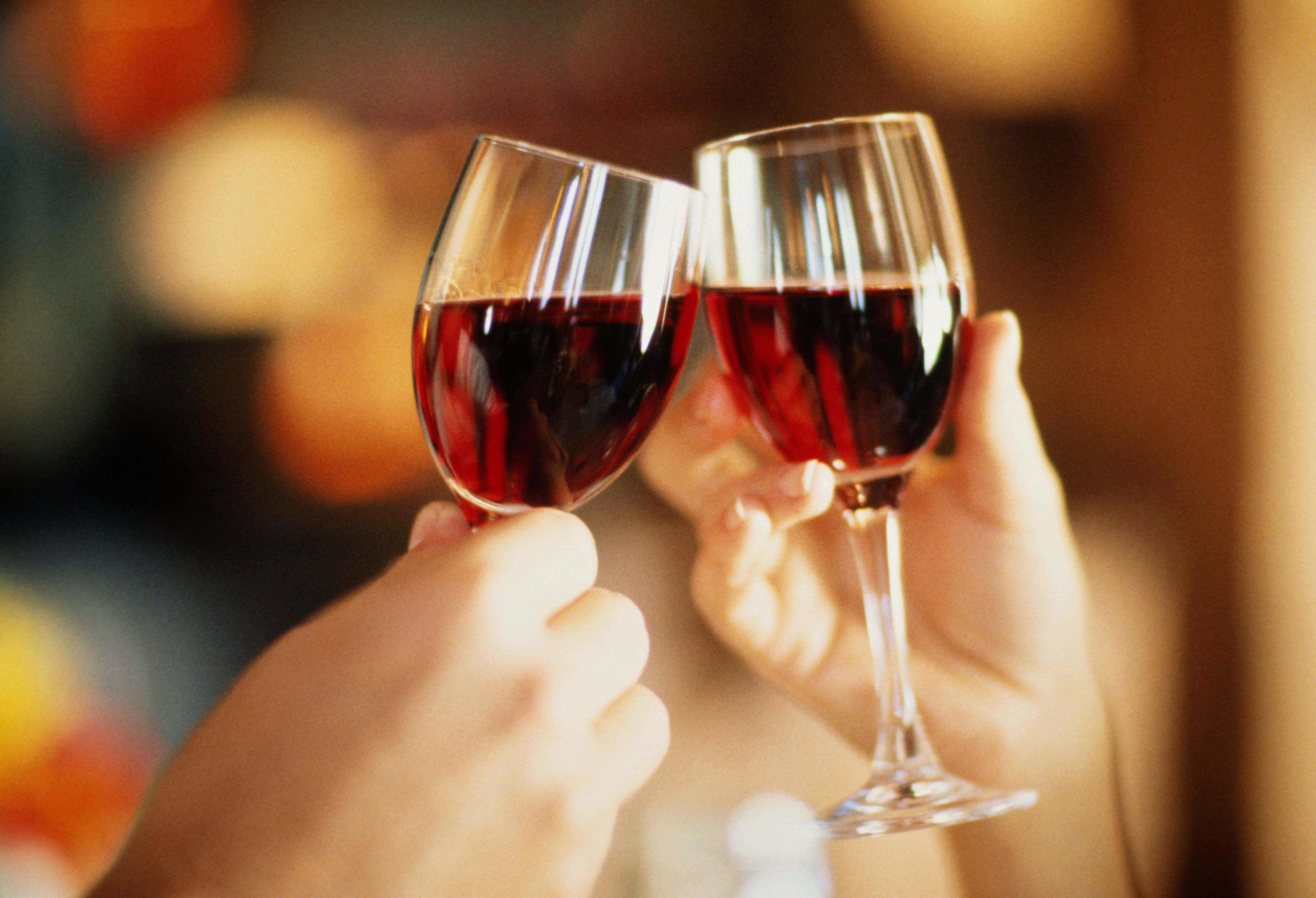 Two people clinking wine glasses