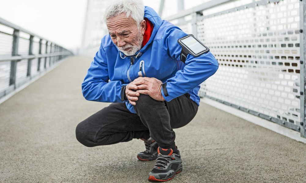 Senior man holding his painful knee after running