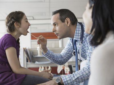 Pediatrician checking patients mouth in office
