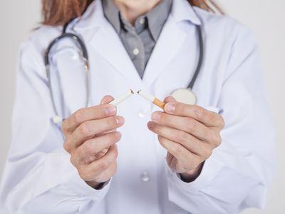 Doctor breaking cigarette
