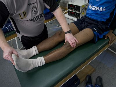 Photo of PT working with a man's knee.