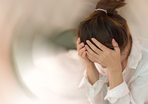 Photo of a woman with her head in her hands and a blurred background suggesting dizziness
