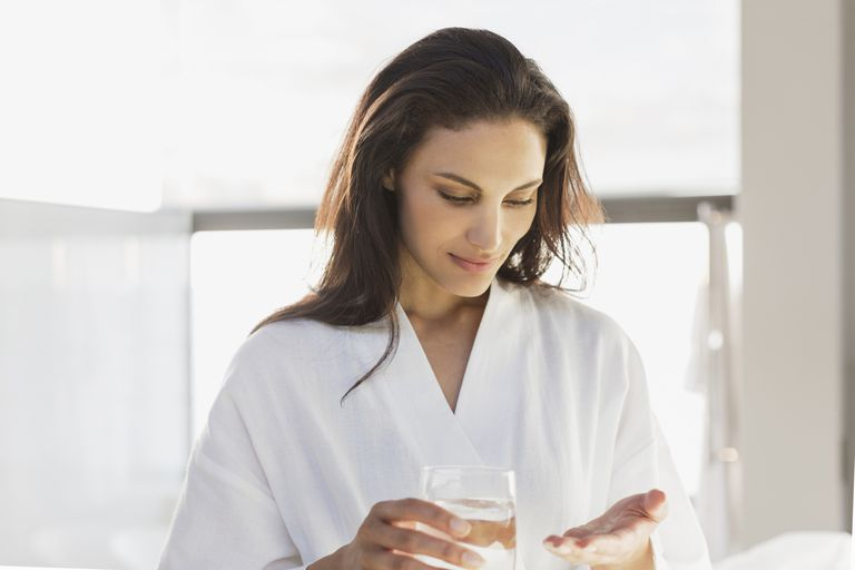 Woman in bathrobe taking vitamin in bathroom