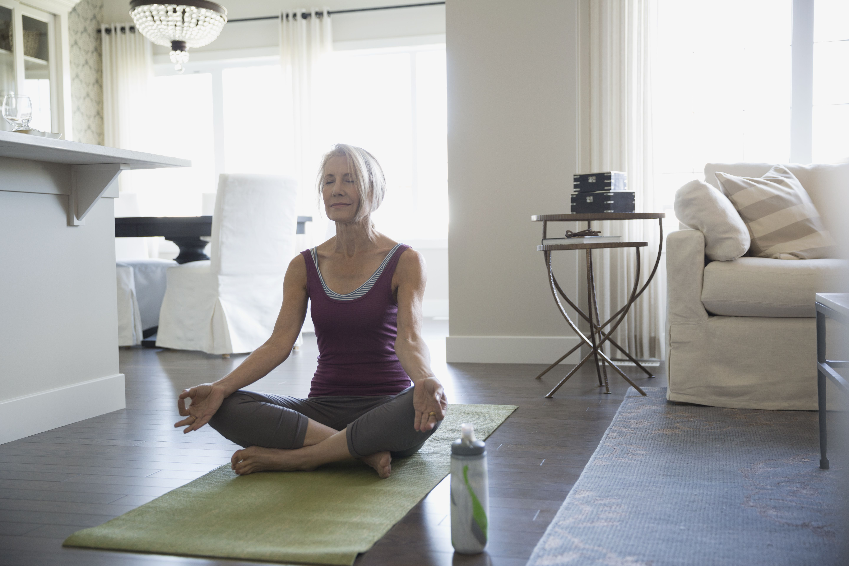 Serene senior woman meditating lotus position living room