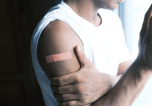An unseen person in a white tank top with a Band Aid on their exposed arm.