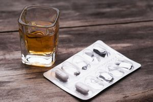 Whiskey or bourbon in a shot glass and pack of pills