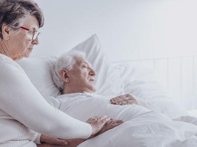 Elderly woman supporting sick husband