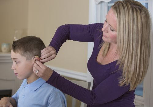mother fitting deaf son with hearing aid