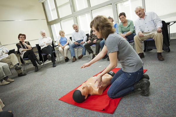 Group of people watching CPR demonstration
