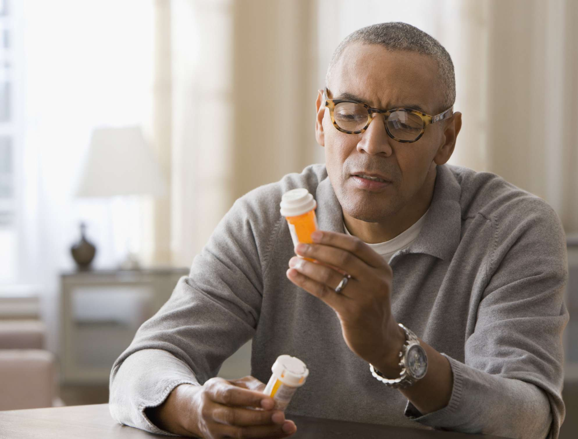 A middle-aged Black man with glasses reading the label on a prescription bottle of medication.