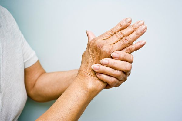 Woman rubbing her arthritic hand