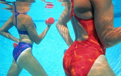 two women power walk in the water.