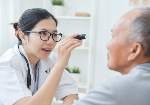 Eye doctor consulting with older man