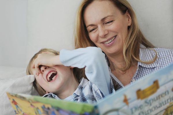 Mother reading story to laughing son