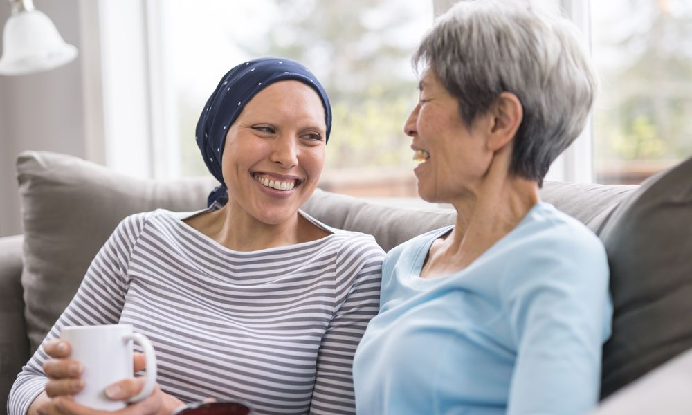 Ethnic woman with cancer laughing with her mother in living room while drinking tea