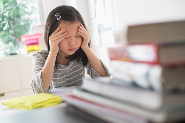 Anxious Chinese student rubbing forehead doing homework